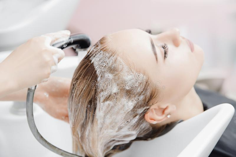 Concept beauty salon. Hairdresser washes hair of beautiful blonde girl under tap in wash stock photos