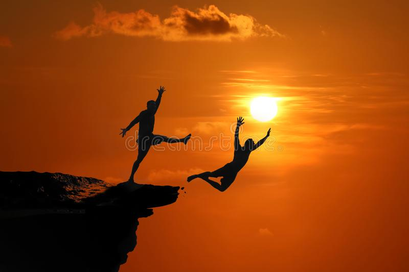 The concept of betrayal and the help of friends, Silhouette of Men are jumped between high cliff at a red sky sunset. Background royalty free stock photos