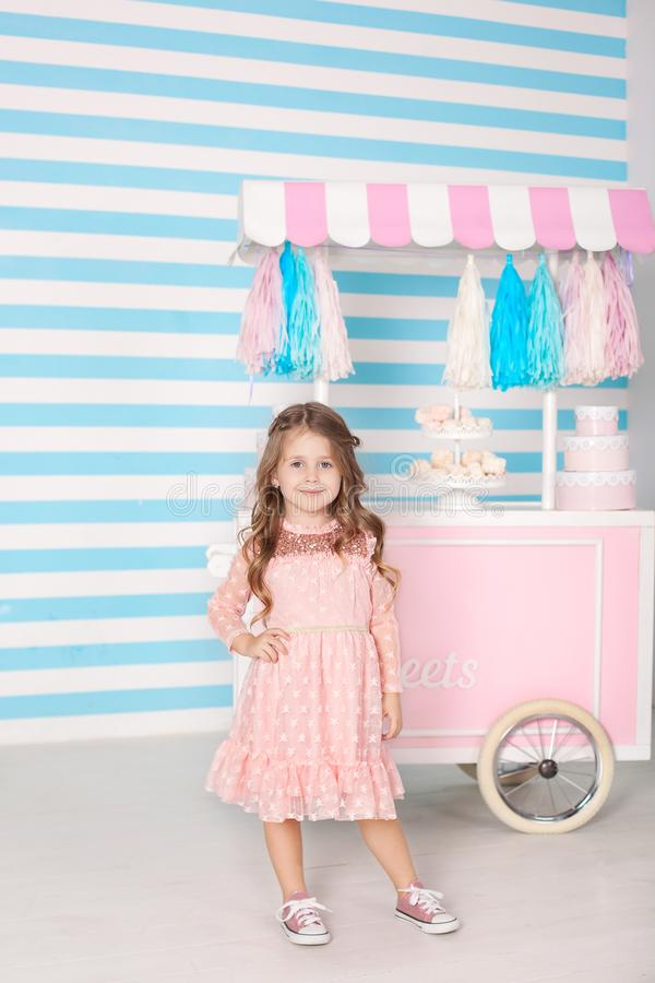 The concept of birthday and happiness - a happy little girl is standing in a beautiful dress on the background of Candy Bar. Decor. Ated room for a birthday girl royalty free stock photo