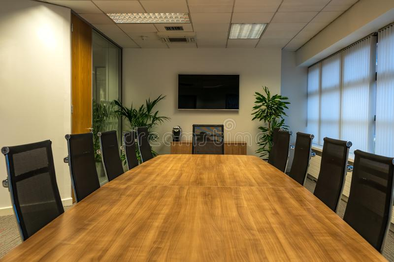Modern interior of boardroom, meeting or seminar room with chairs and long wooden table at workplace or office, green plants and T. Concept of boardroom or stock photography