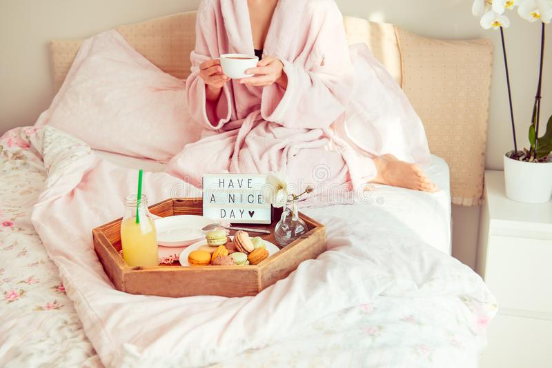 Concept bonjour Le petit déjeuner dans le lit avec ont un texte de beau jour sur la boîte allumée, le jus et les macarons sur le  photographie stock