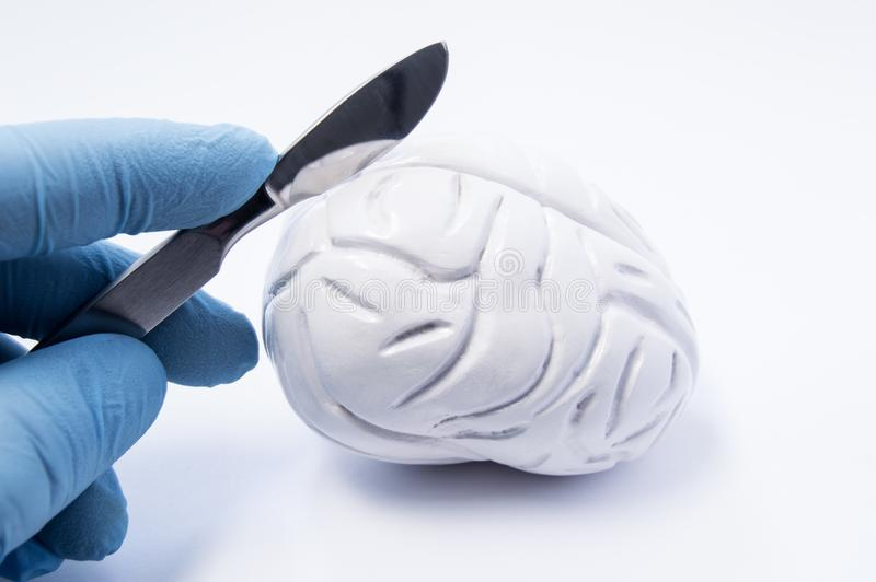 Concept of brain surgery or neurosurgery. Neurosurgeon holding scalpel in hand over 3D anatomical model of human brain. Brain surg. Ery operations for treatment royalty free stock photography