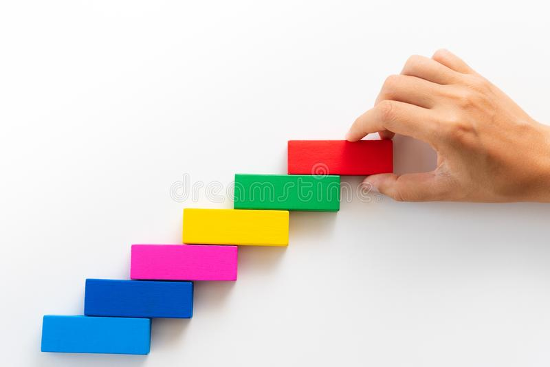 Concept of building success foundation. Women hand put red wooden block on colorful wooden blocks in the shape of a staircase. royalty free stock photos