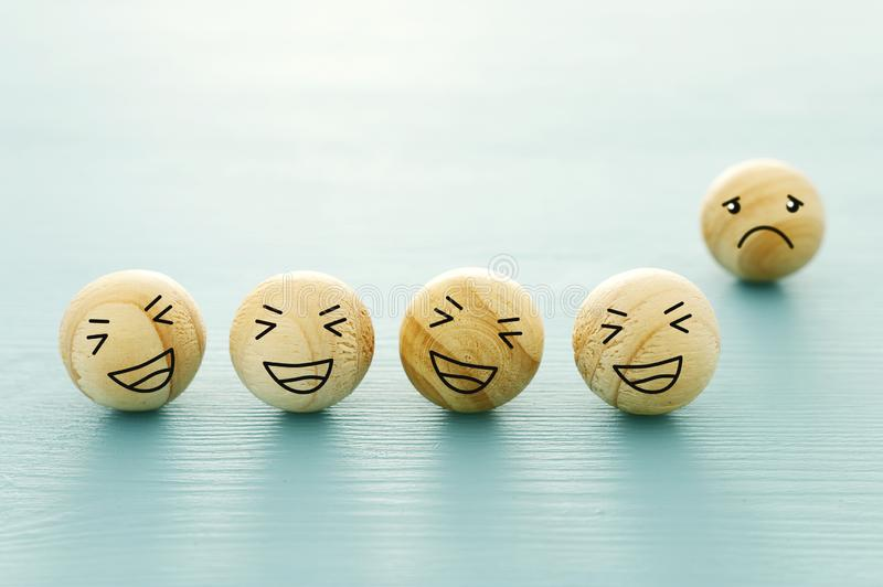 Concept of bullying. group of laughing faces and one alone stock image