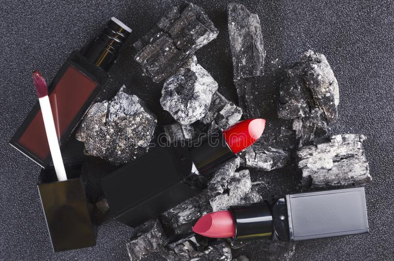 Concept of burning sale of cosmetics.Black friday concept.Red lipsticks on the hot charcoal stock photos