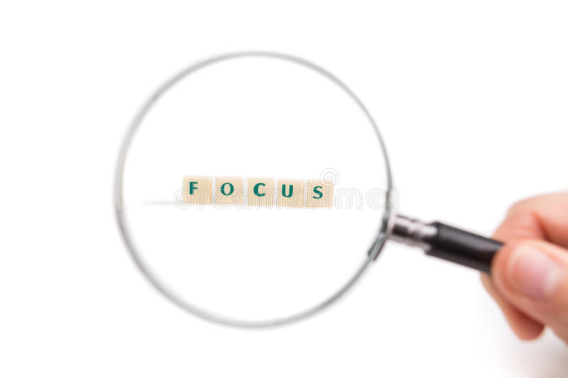 Concept of business idea focus. Magnifying glass in hand on the letters. White background stock image