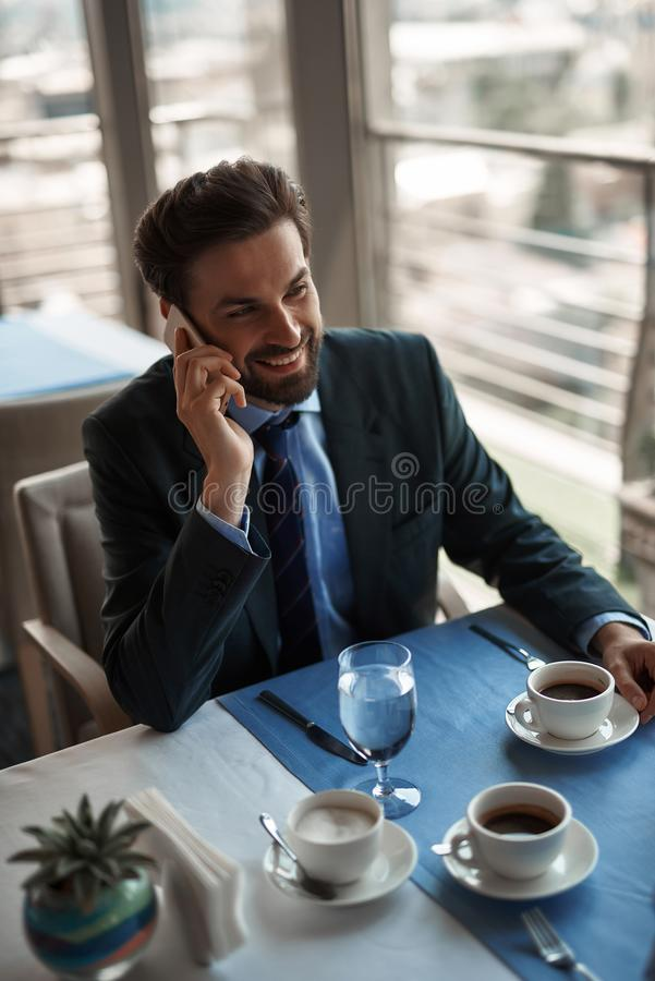 One man having business lunch in restaurant. Concept of business lunch. Top angle portrait of young smiling businessman talking by phone while sitting in stock photos