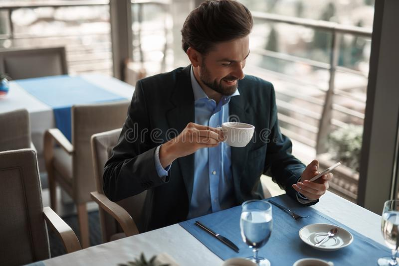 Smiling male having business lunch in restaurant. Concept of business lunch. Waist up portrait of young smiling businessman checking massages on phone while royalty free stock image