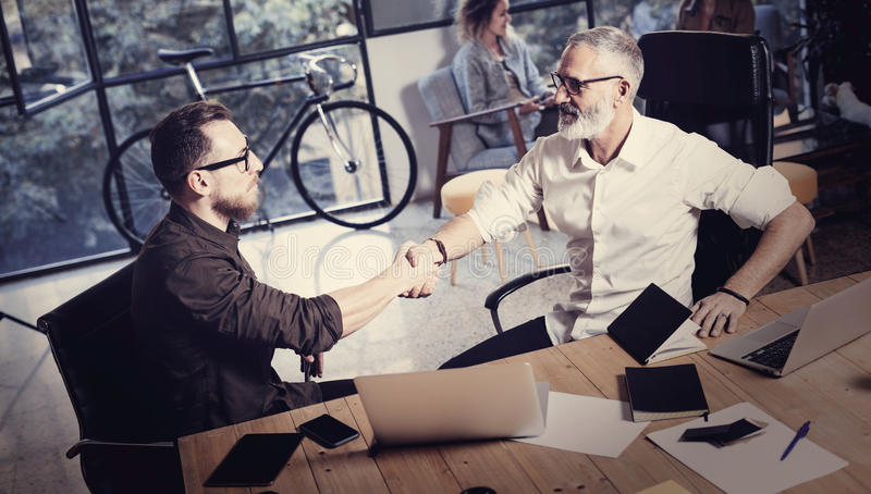 Concept of business partnership handshake.Photo two bearded businessmans handshaking process.Successful deal after great. Meeting in modern office.Horizontal royalty free stock photography
