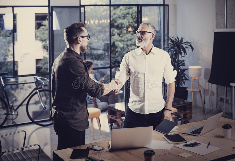 Concept of business partnership handshake.Photo two businessmans handshaking process.Successful deal after great meeting. In coworking studio.Horizontal stock photo