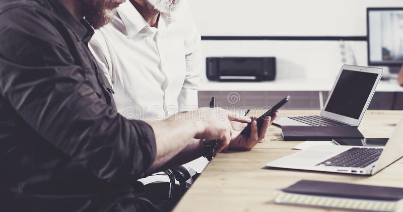 Concept of business people meeting process.Bearded young man holding mobile phone and touching screen.Adult businessman stock photos
