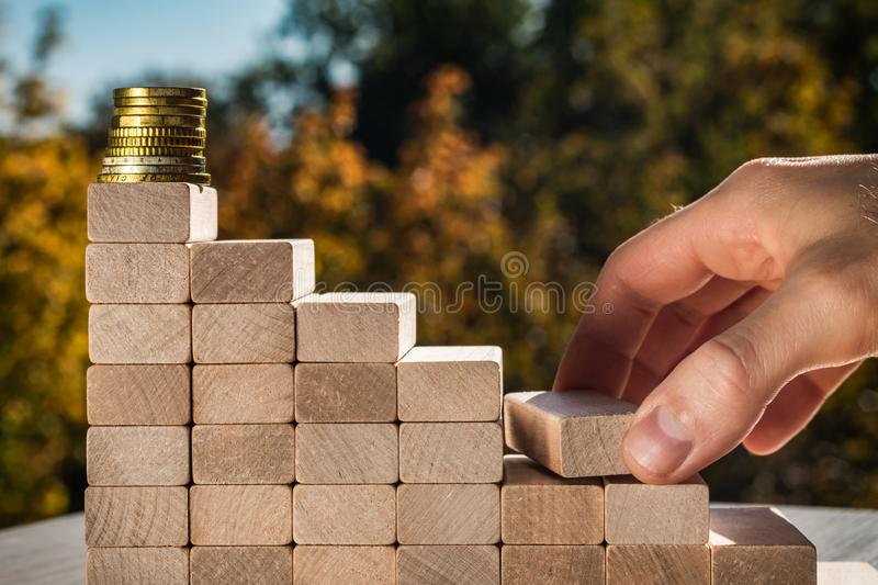 Concept of business promotion goals. Male fingers build stairs made of wooden blocks leading to the top. Blurry autumn background stock images