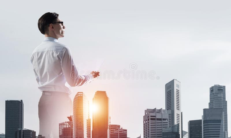 Concept of business success and control with confident boss against cityscape background stock photography