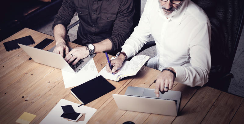 Concept of business teamwork.Two bearded businessmans discussing ideas together in modern office.Adult man making notes. In paper notebook,using gadgets at royalty free stock images