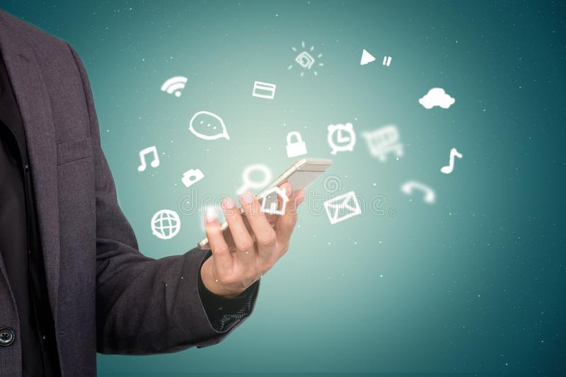 Concept of businessman holding mobile smart phone with life style application icon around stock photo
