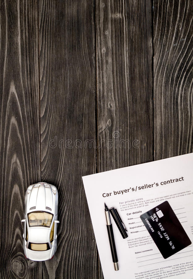 Concept of buying car on dark wooden background top view.  royalty free stock images