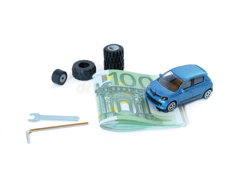 Concept car repair costs. A model car on 100 Euro notes next to tires and tools royalty free stock images