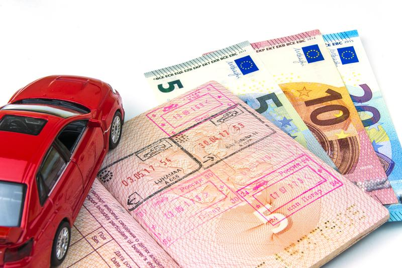 The concept of car travel: the passport with the border stamps. A few bills-Euro cash. Red car model. On white background stock photo