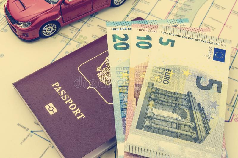 The concept of car travel: the passport and map. A few bills-Euro cash. Red car model. Soft processing in retro style royalty free stock photo