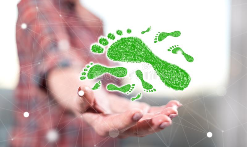 Concept of carbon footprint. Carbon footprint concept above the hand of a woman in background stock photography