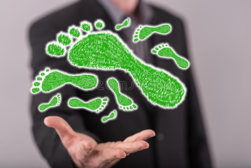 Concept of carbon footprint. Carbon footprint concept above the hand of a man in background royalty free stock images