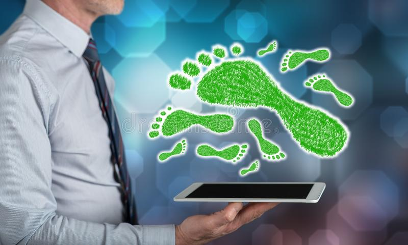 Concept of carbon footprint. Carbon footprint concept above a tablet held by a man royalty free stock photography