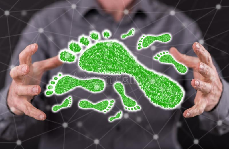 Concept of carbon footprint. Carbon footprint concept between hands of a man in background royalty free stock photo