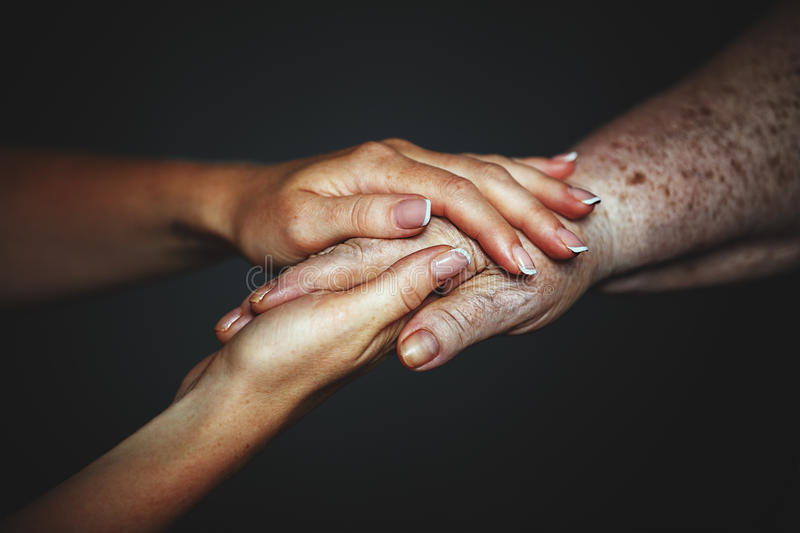 Concept of care for older people. Hands of the old and a young w stock photos