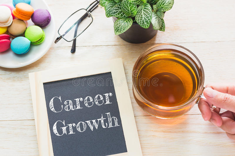 Concept Career Growth message on wood boards. Macaroons and glass Tea on table. royalty free stock images