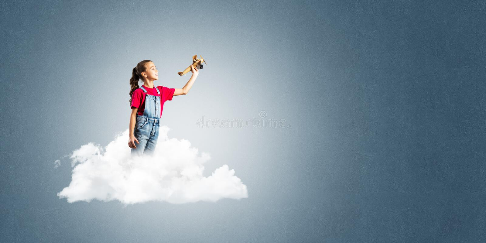 Concept of careless happy childhood with girl dreaming to become pilot. Cute kid girl standing on cloud and playing with airplane toy royalty free stock photos