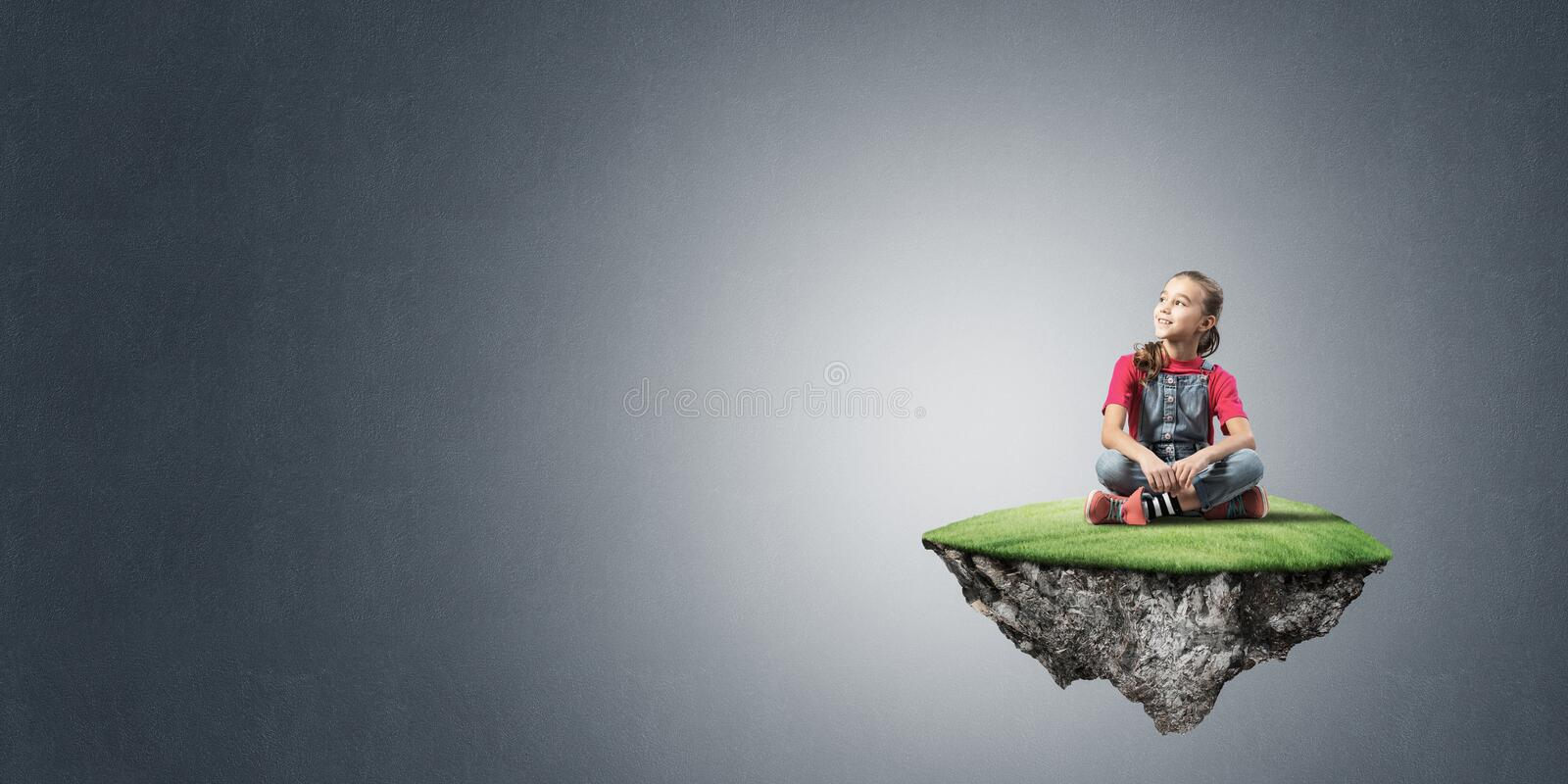 Concept of careless happy childhood with girl on flying island. Cute kid girl sitting on flying island and looking away royalty free stock photos