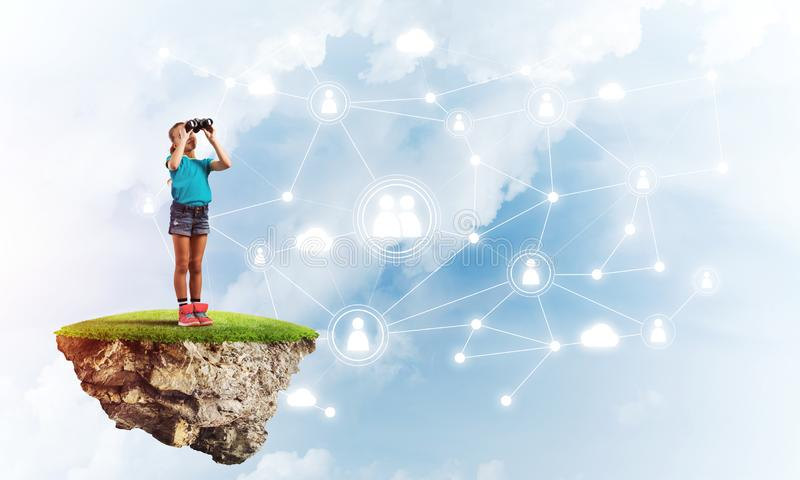 Concept of careless happy childhood with girl looking in binoculars royalty free stock image