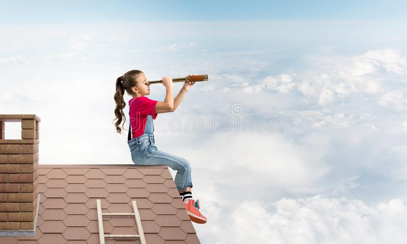 Concept of careless happy childhood with girl looking in spyglass royalty free stock photos