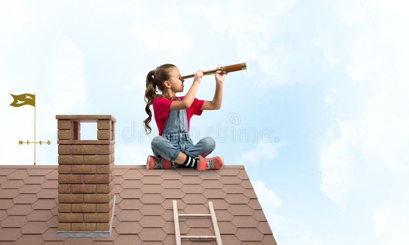 Concept of careless happy childhood with girl looking in spyglass stock images