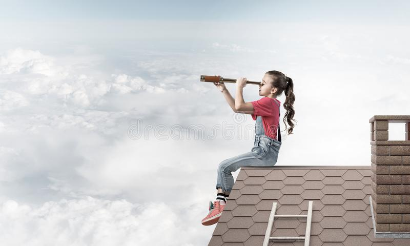 Concept of careless happy childhood with girl looking in spyglass stock photo