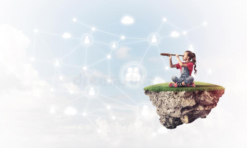 Concept of careless happy childhood with girl looking in spyglass royalty free stock photography