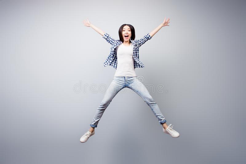 Concept of careless and madness. Crazy asian young girl is having fun. She is dressed in checkered shirt and jeans, she is royalty free stock photography