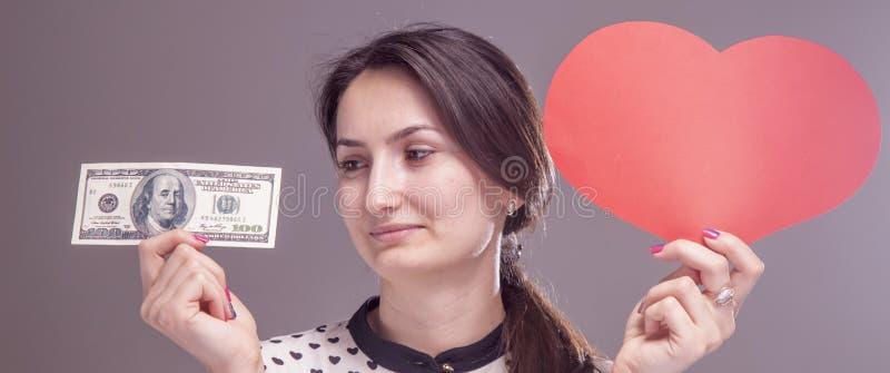 Concept: carrière versus het persoonlijke leven Mooie vrouw met hart en contant geld als symbool van keus tussen succes en bedrij stock fotografie