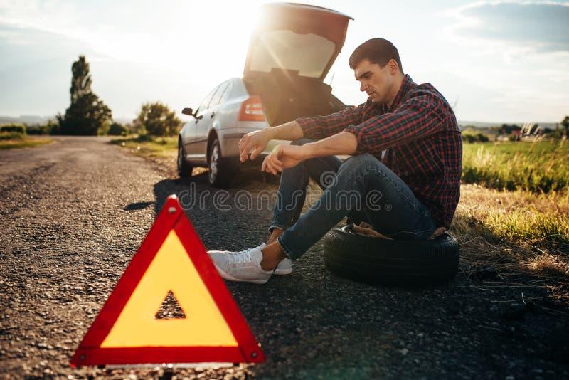 Concept cassé de voiture, homme s'asseyant sur le pneu image stock