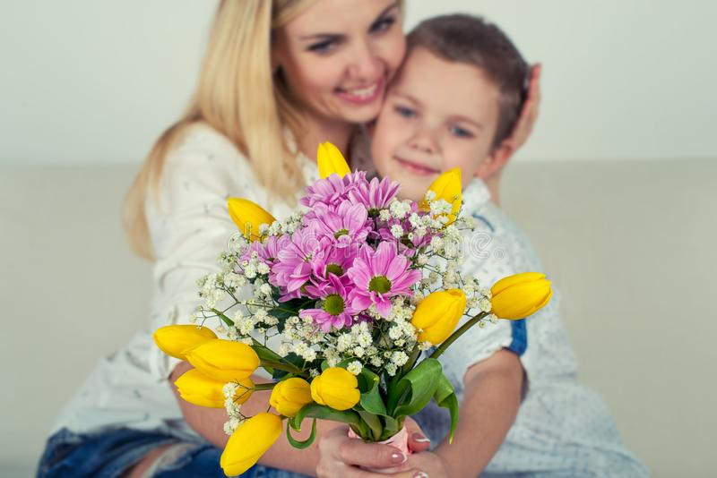 Son gives his beloved mother a beautiful bouquet of tulips.The concept of the celebration,women`s day. royalty free stock photos