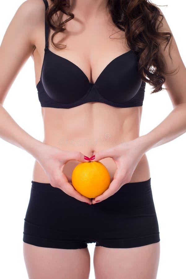 Concept cellulite De slanke sinaasappel van de meisjesholding royalty-vrije stock afbeelding