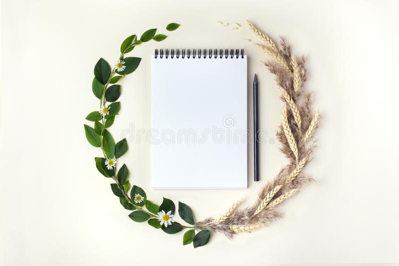 Concept of changing seasons from summer to autumn. Top view. The concept of changing seasons from summer to autumn in the form of wreath with sketchbook and royalty free stock images