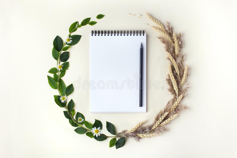Concept of changing seasons from summer to autumn. Top view. The concept of changing seasons from summer to autumn in the form of wreath with sketchbook and royalty free stock photos