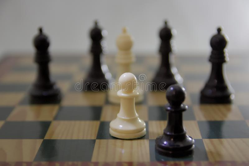 Two black and white pawns against 5 bishops on the chess board stock photos