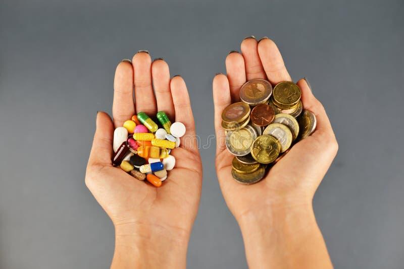 Concept cher de traitement avec des piles d'argent d'argent liquide et de drogues pharmaceutiques chez des mains de la femme photos libres de droits