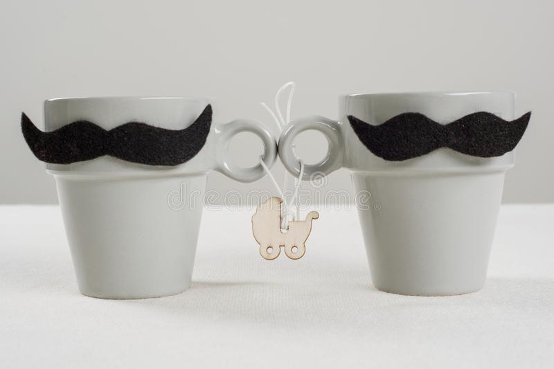 The concept child in homosexual family. Symbolic cups with a mustache, stroller with baby. royalty free stock images