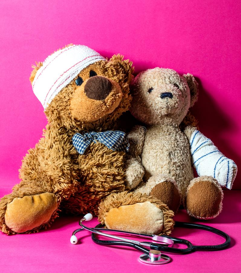 Concept of child playing doctor with teddy bears and bandage. With a stethoscope for education to healthcare or hospital over pink background royalty free stock photography