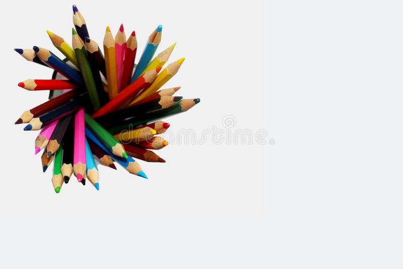 Colour pencils in a glass on white background. Top view stock image