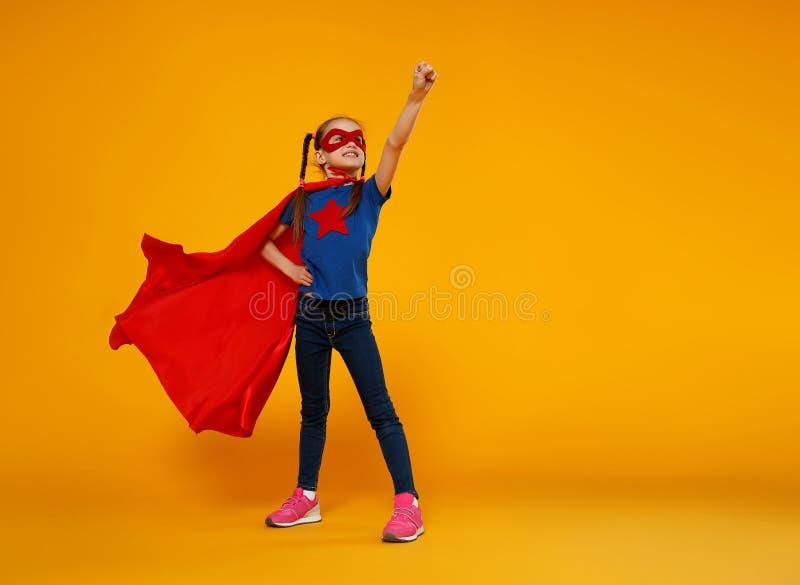 Concept of child superhero costume on yellow background stock image