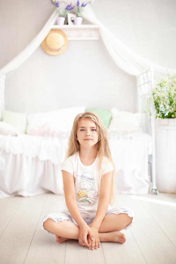 The concept of childhood and health. The child does yoga and meditation at home. A little blonde girl in pajamas sits in a pose fo royalty free stock photography